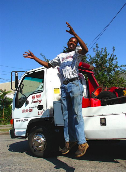 Ron Brown leaps into the air in front of his tow truck.