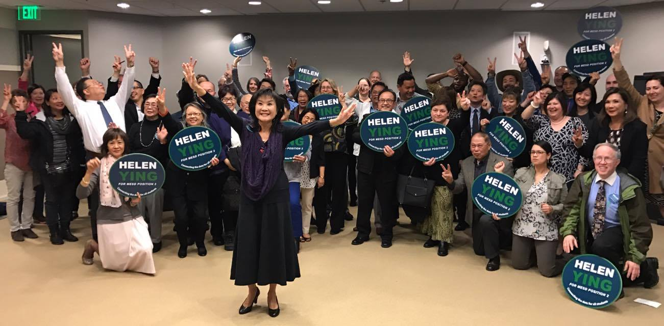Helen Ying stands in front of a crowd of her supporters, arms outstretched.
