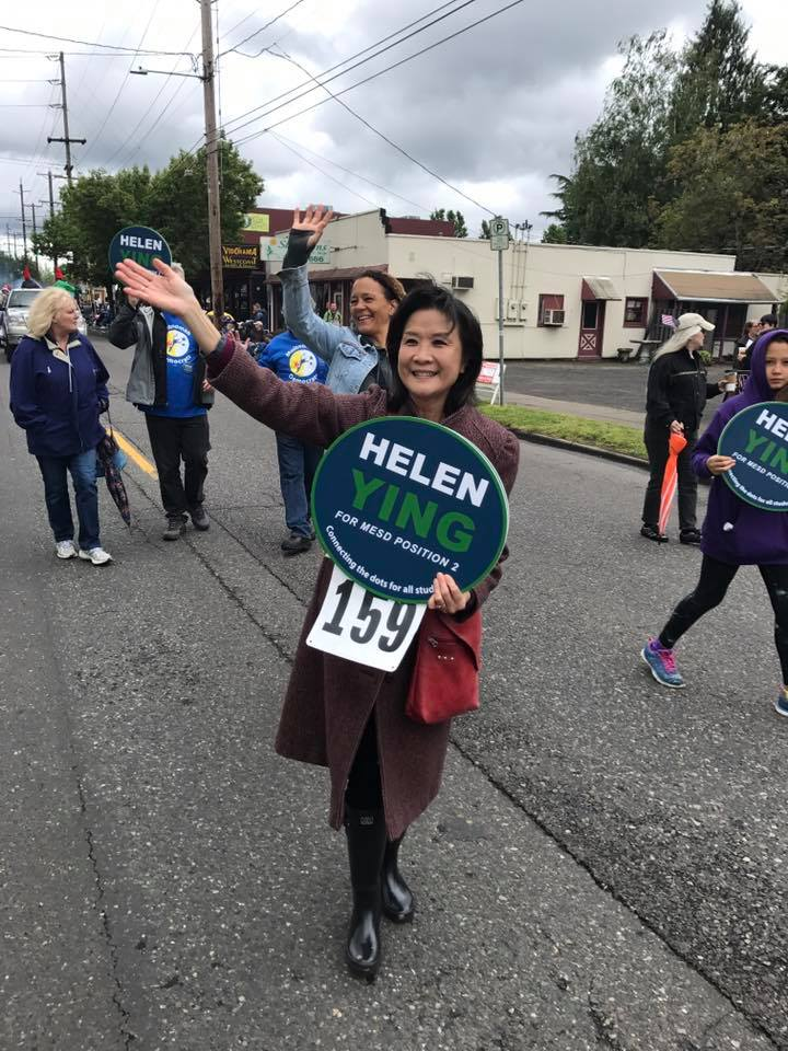 Helen marches in the St. Johns Parade, waving with one hand and holding a campaign sign in the other.