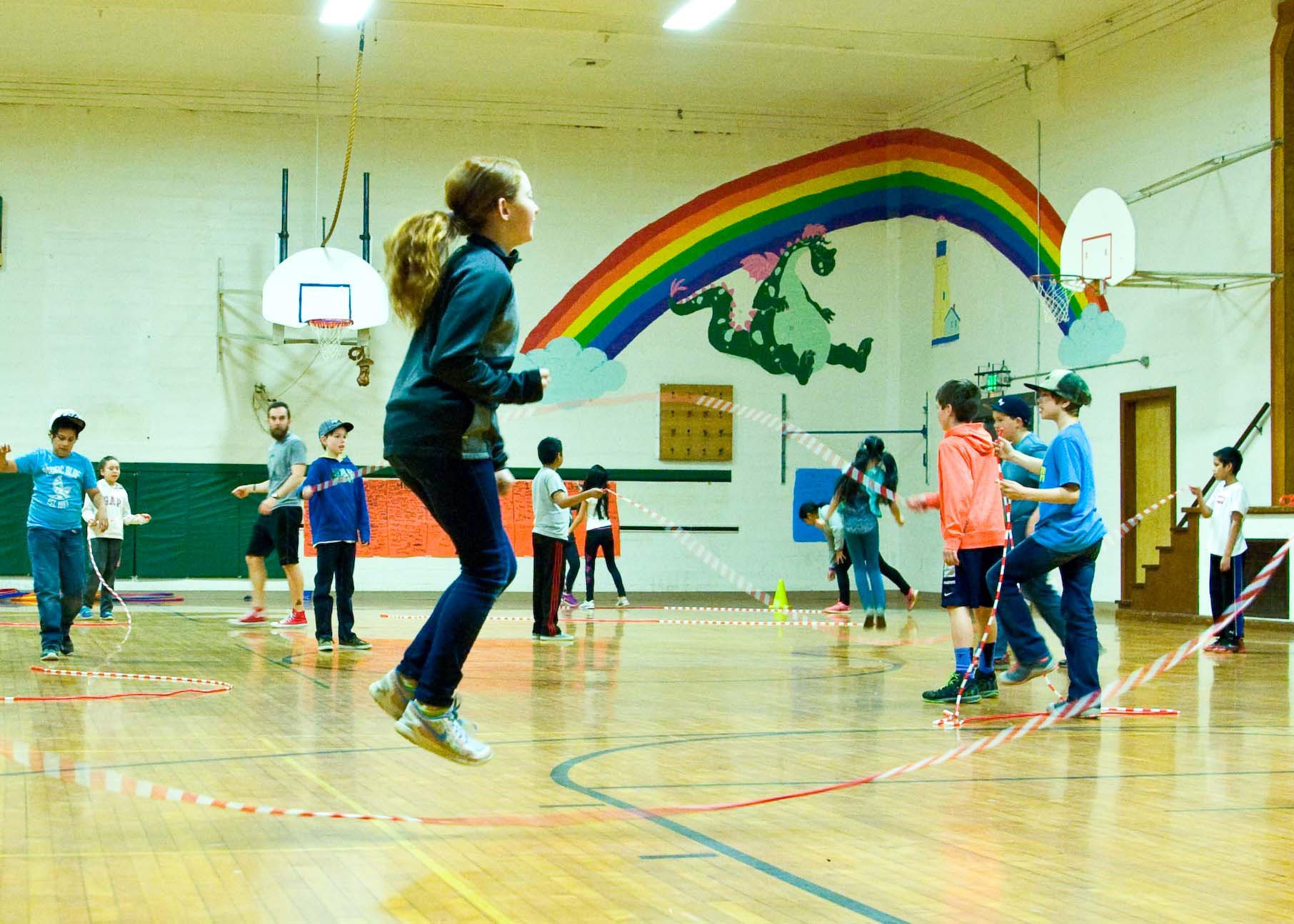 Parkdale students jump rope in a gym. A rainbow and dragon are painted on the wall above the basketball hoops.