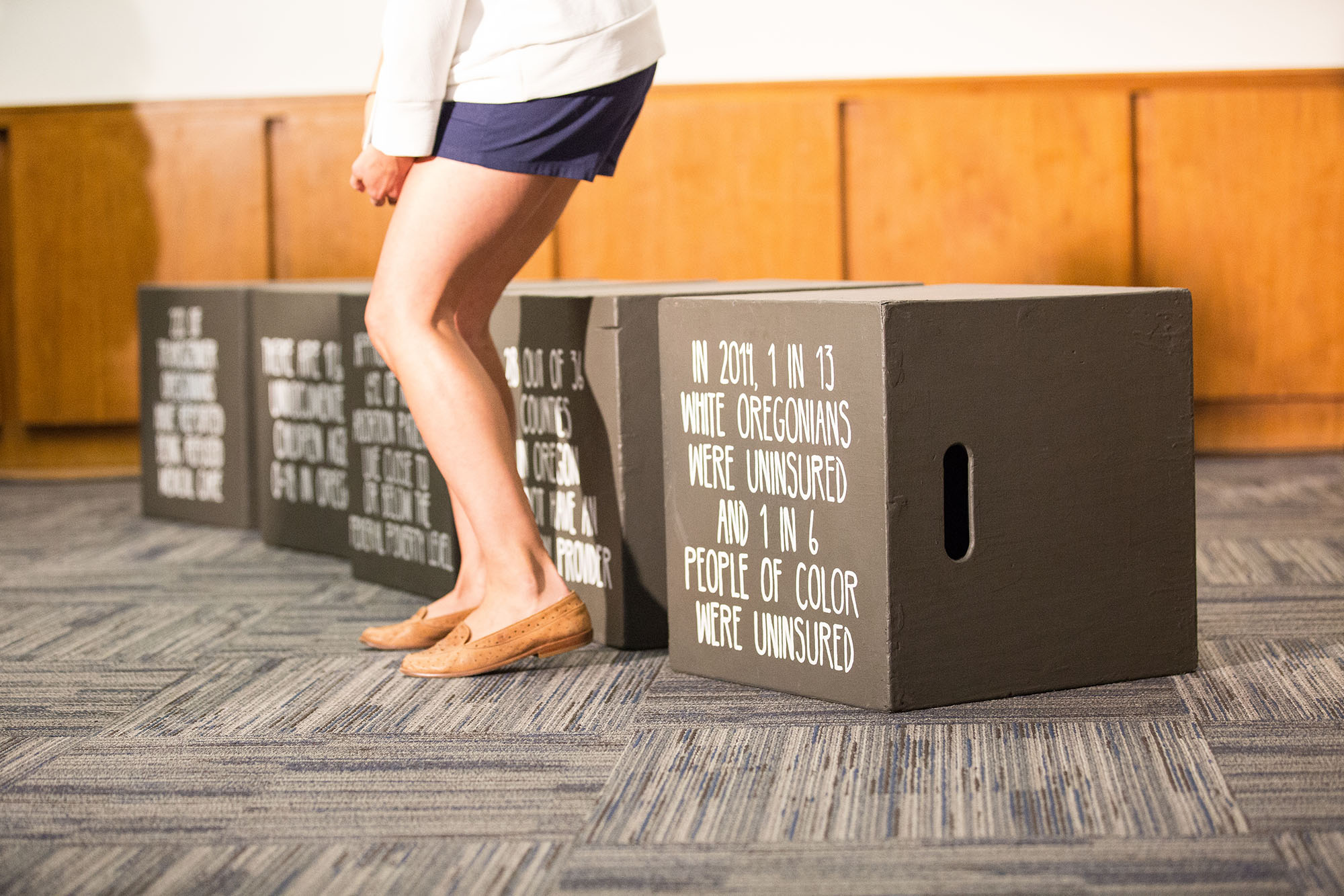 "A person stands in front of a row of gray boxes, visible from the waist down. Each box has a  statistic painted on it. The closest one reads, ""In 2011, 1 in 13 white Oregonians were uninsured and 1 in 6 people of color were uninsured."""