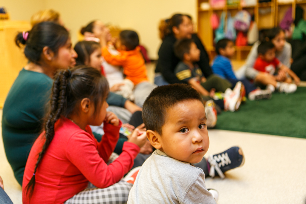 Parents and children sit in a semicircle on the floor of a classroom.