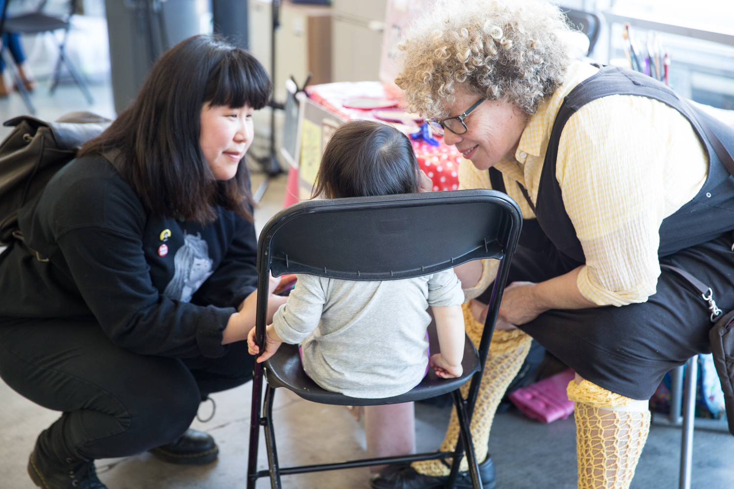 Two adults crouch on either side of a toddler seated in a folding chair.