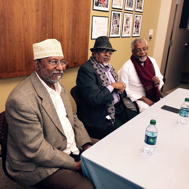 Three members of the Somali community sit on one side of a white tablecloth-covered table.