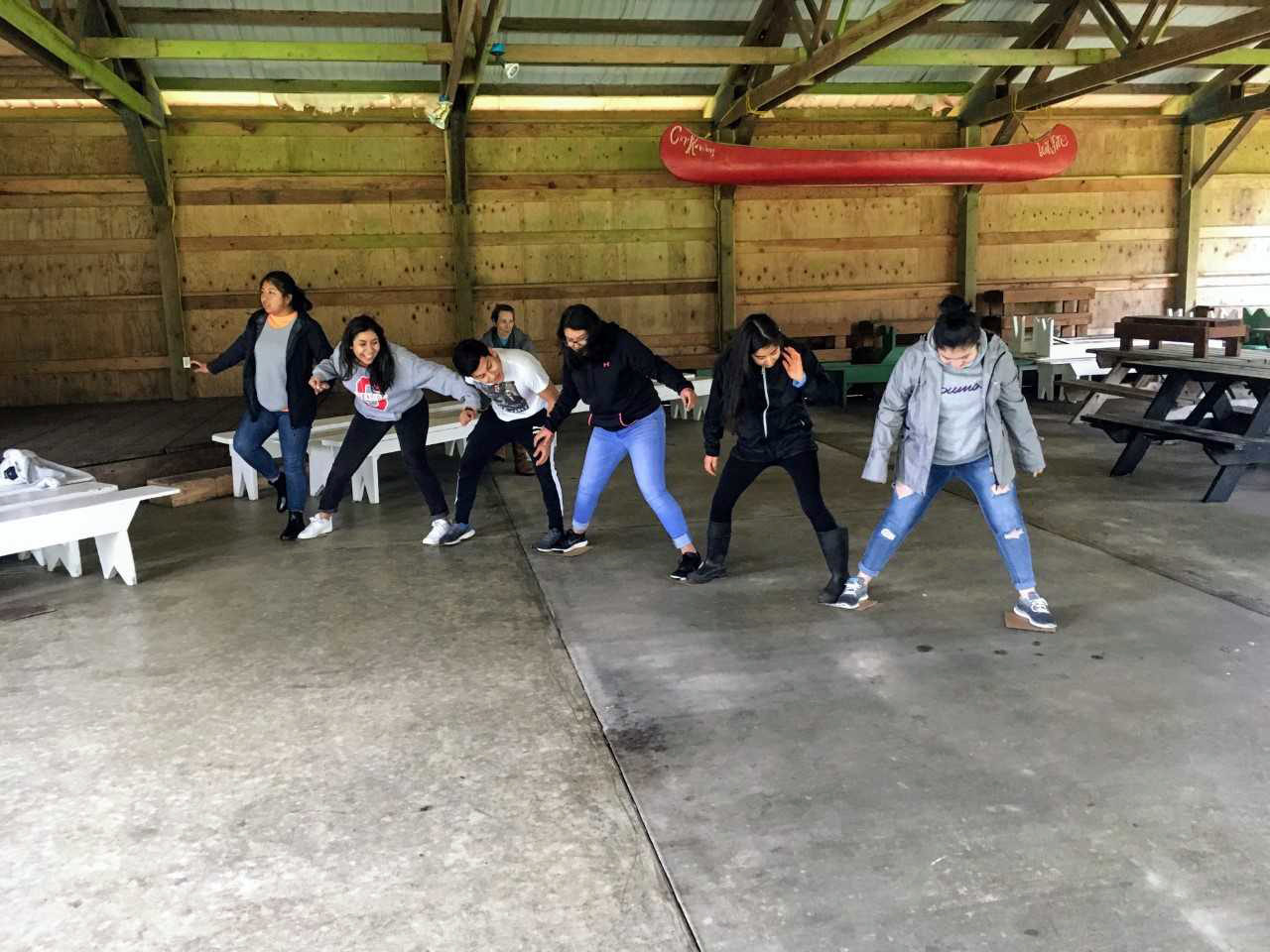 Six Latinx youth stand in a row, foot to foot, their legs spread wide. They're inside a wooden shelter with picnic tables.