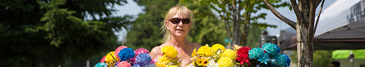 A woman wearing sunglasses carries bunches of flowers.
