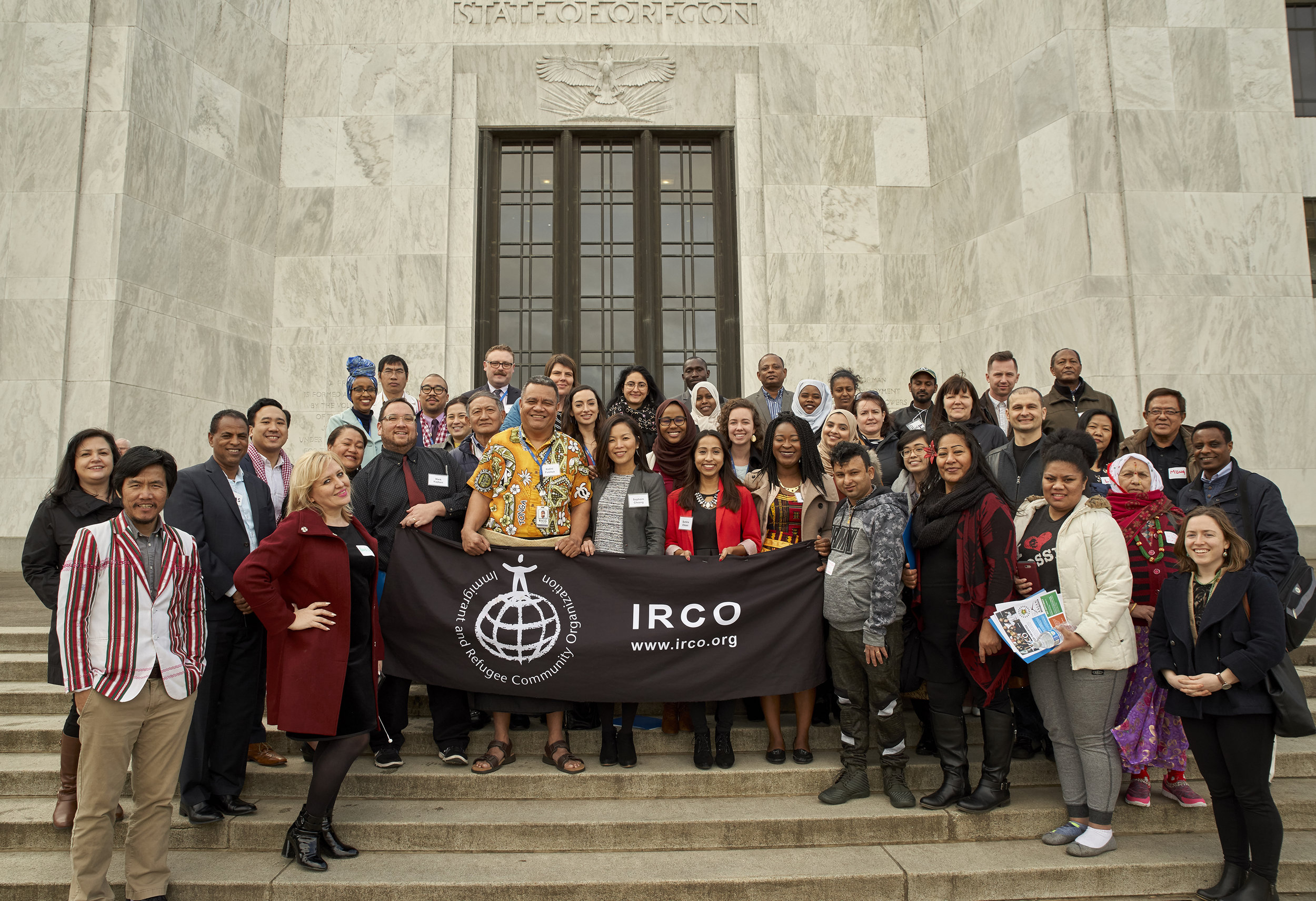 Members of the Multiethnic Advisory Group stand on the steps of Oregon's State Capitol building holding an IRCO banner.