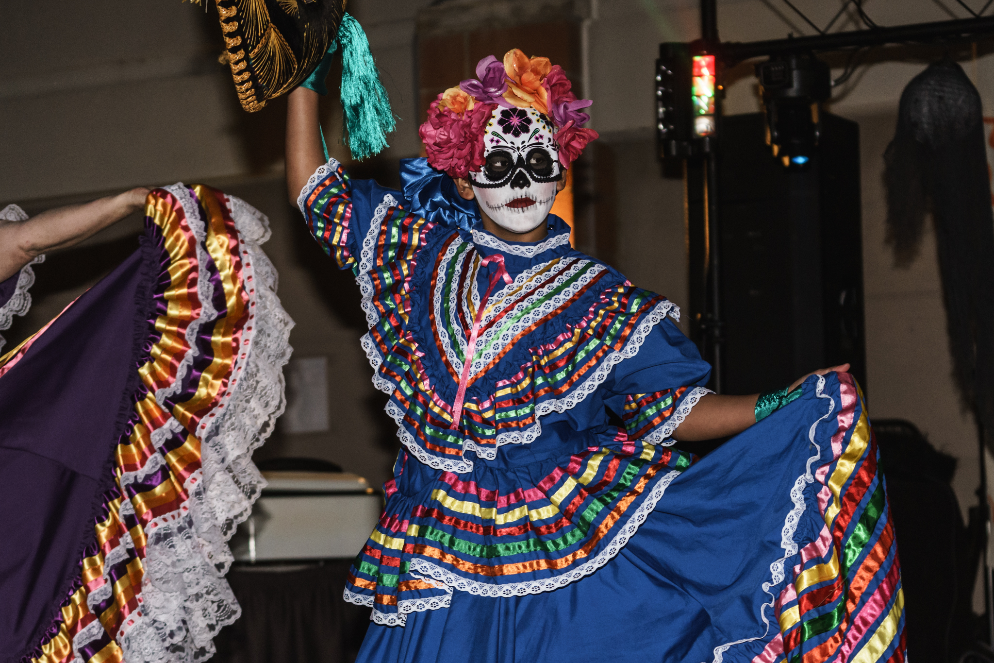 A dancer in a Jalisco dress and Sugar Skull mask performs at EUVALCREE's Day of the Dead celebration.
