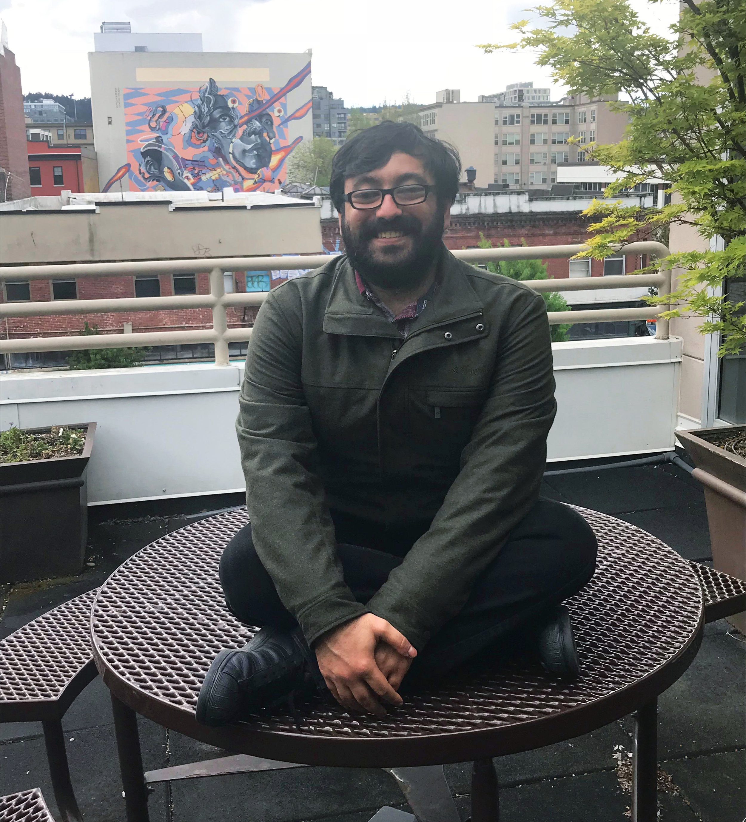 Mohammed sits cross-legged on top of a round picnic table, smiling.