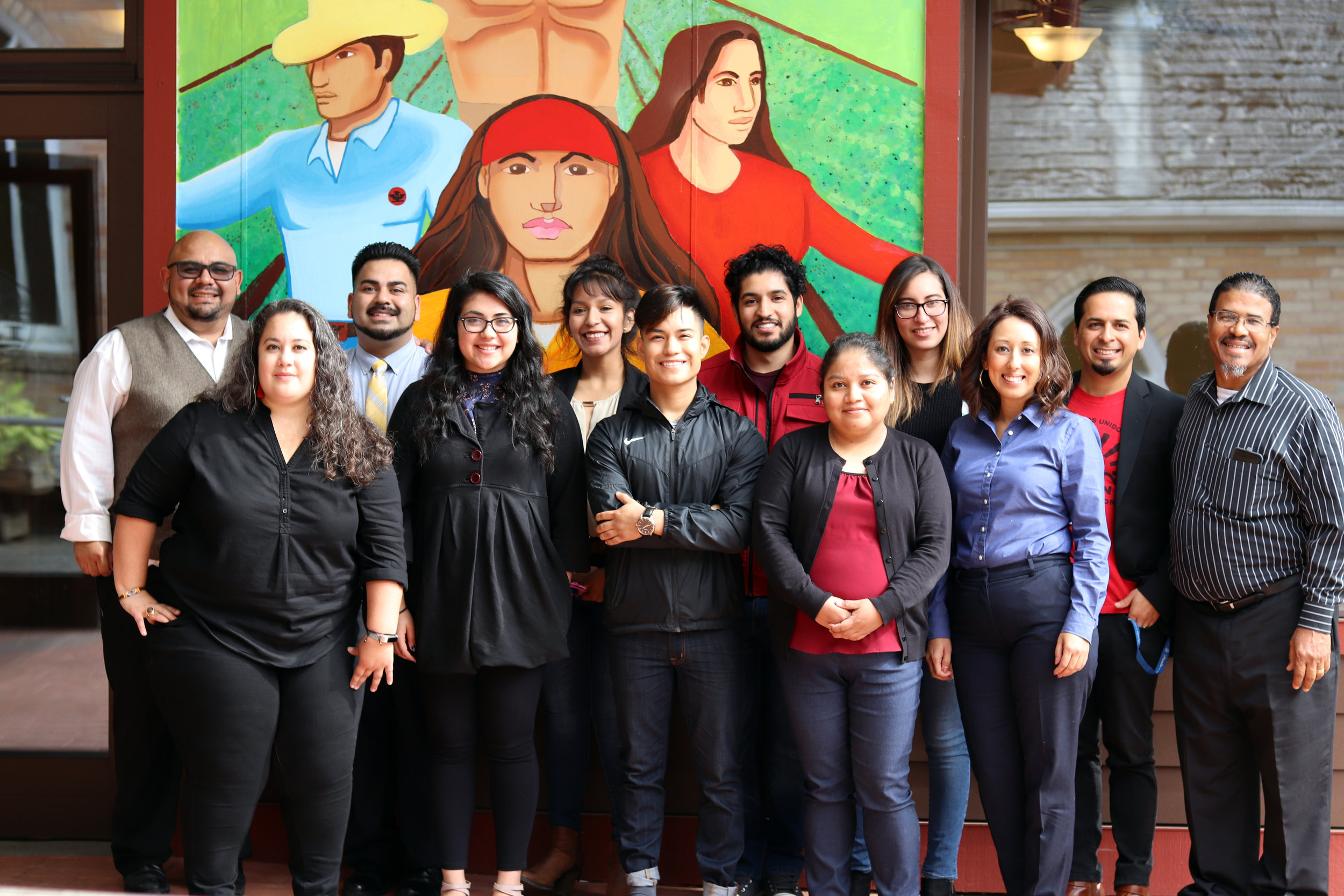 Graduates from People's Representatives' elected office cohort stand and smile in front of a large painting depicting farmworkers.