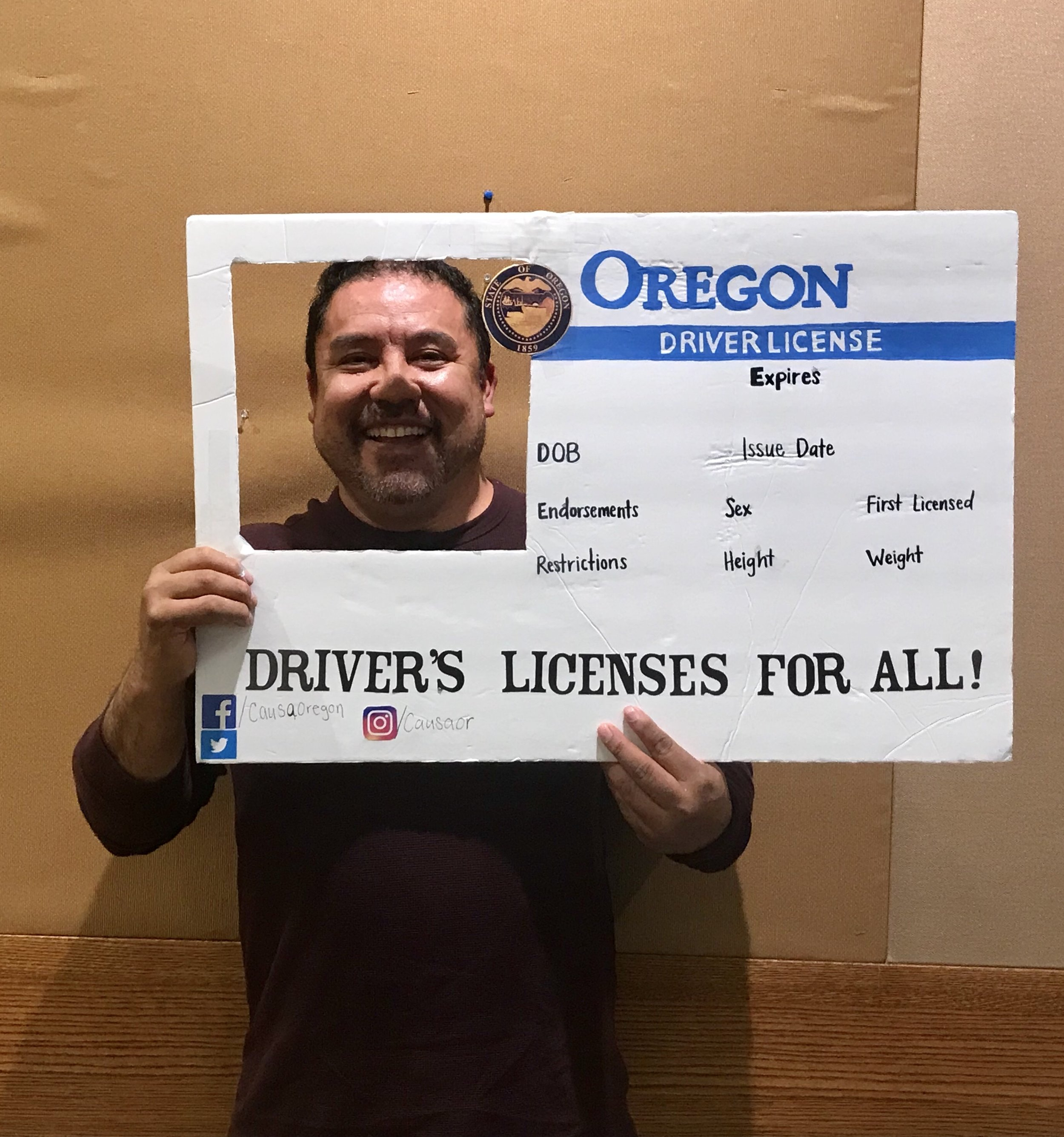 A parent holds up a poster decorated to look like a giant Oregon driver's license. His face is framed by a square cut-out in the upper left corner.