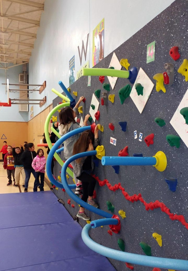 Three Washington Elementary School students scale a climbing wall with pool noodles sticking out of it. Several students wait in line for their turn.