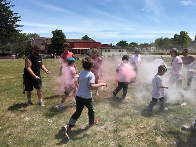 Independence Elementary students run through clouds of colored powder, tossed by adults standing on the sidelines.