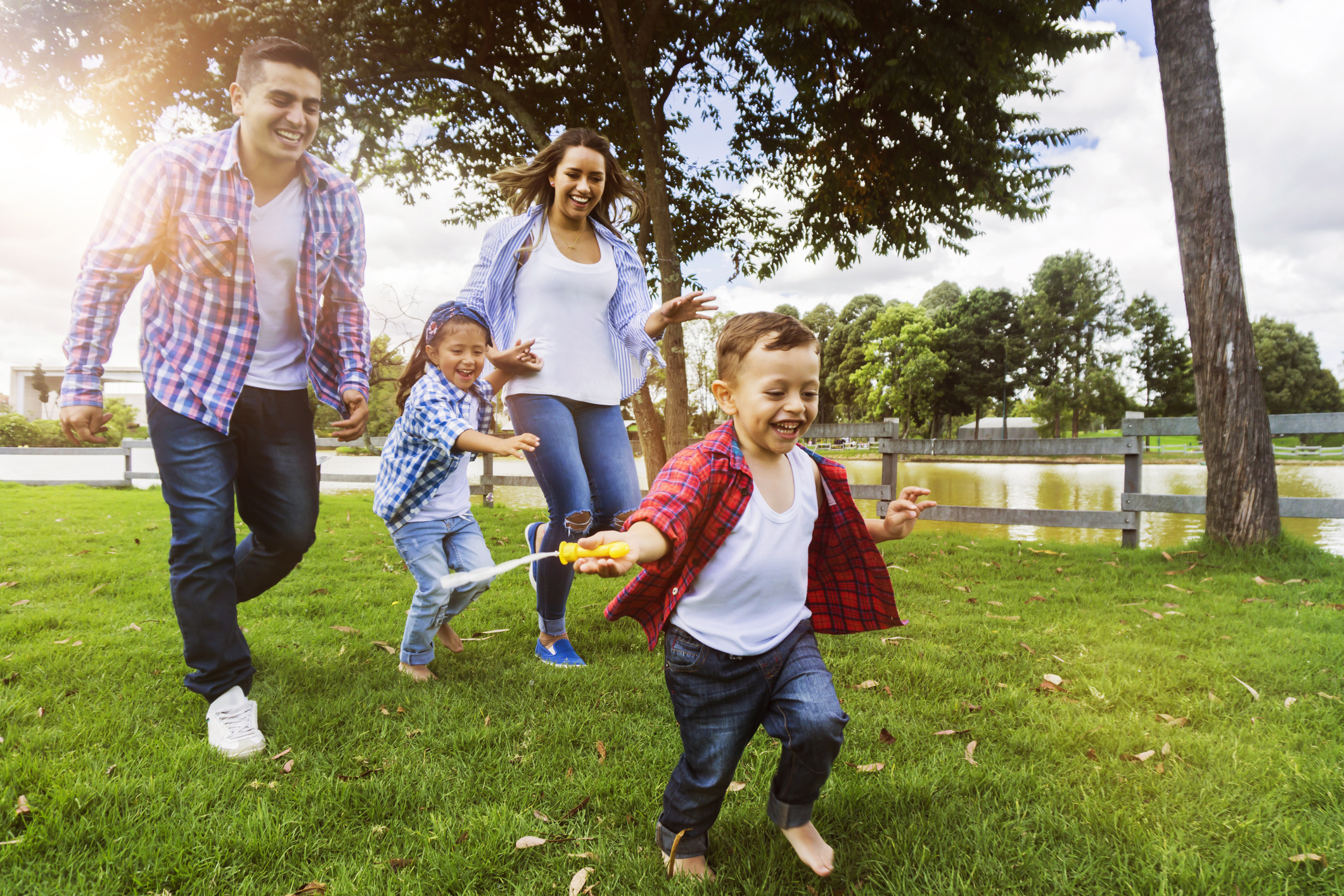A family with two parents and two children runs through a park.