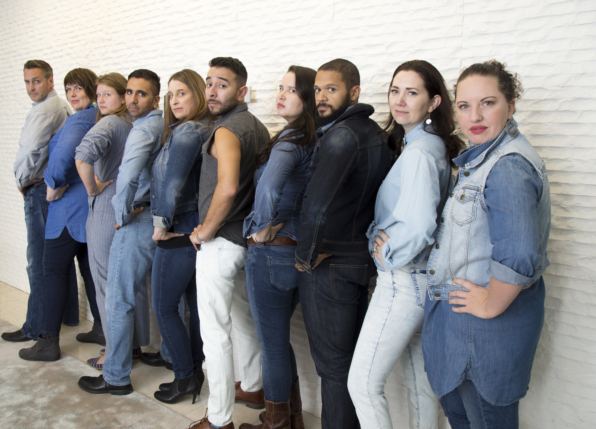 NWHF staff, all dressed in denim, stand in a line along a white brick wall with their backs to the camera. They all look over their shoulders.