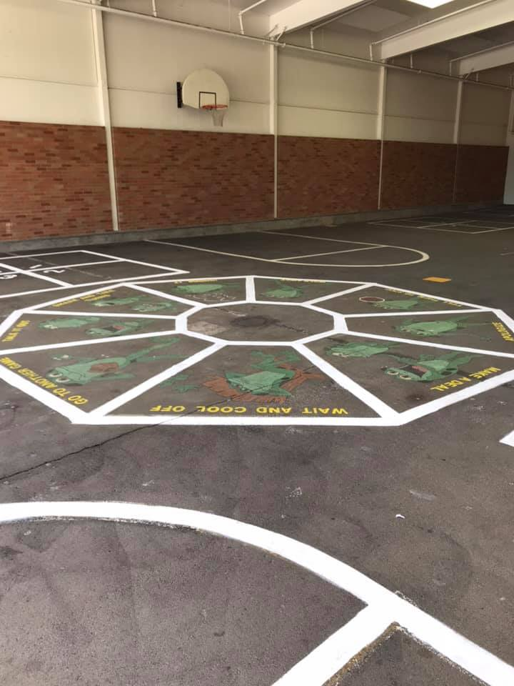 "Whitcomb Elementary's problem-solving wheel painted on the playground blacktop. It includes options like ""Wait and Cool Off"" and ""Make a Deal"" illustrated with frogs."