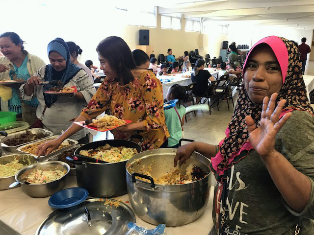 Community members serve themselves food from a buffet line.