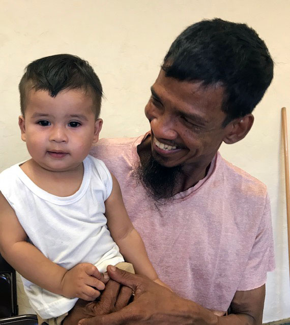 An adult holds a toddler, smiling at them.