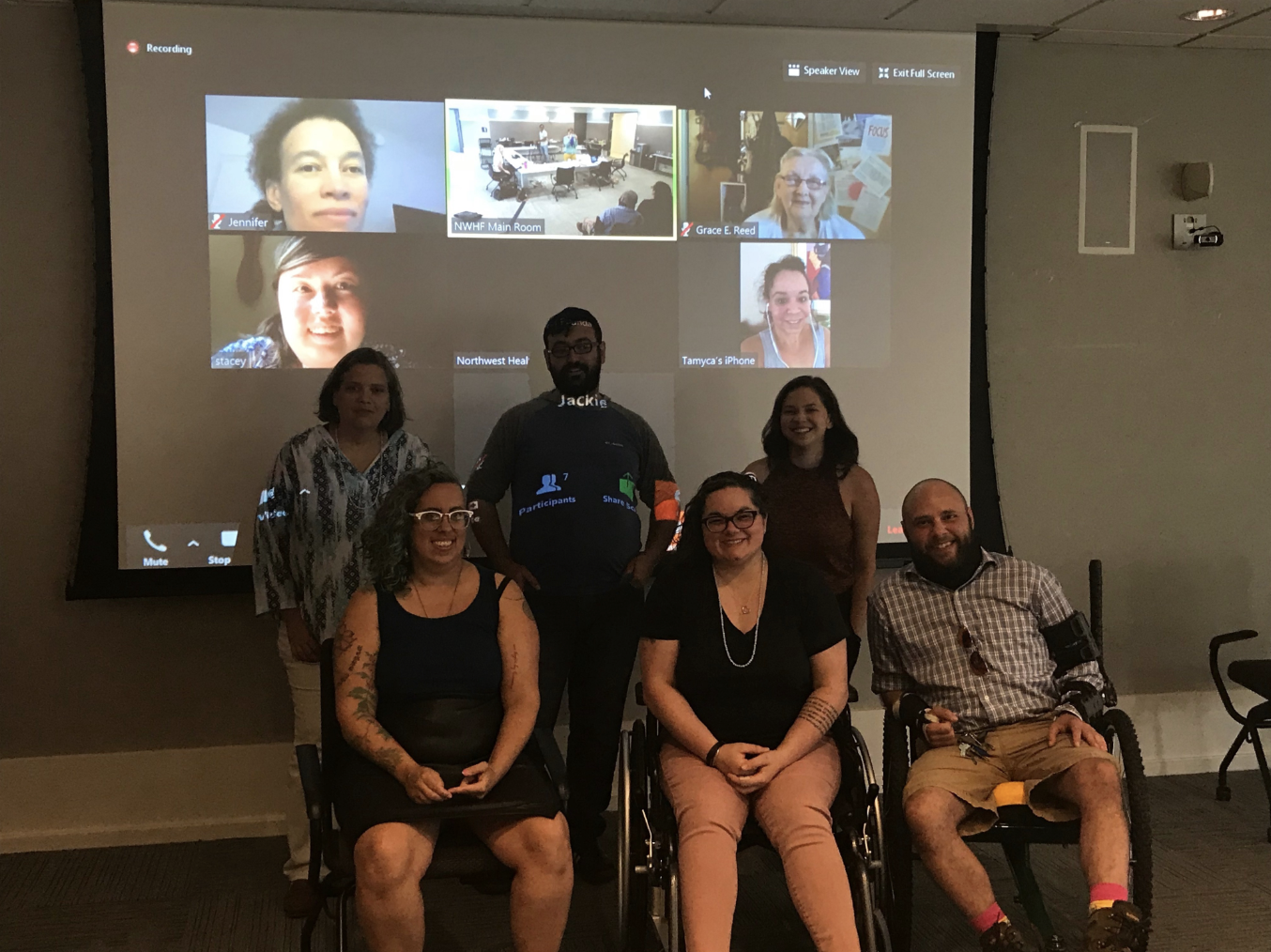 Six people stand and sit in front of a projector screen. Four more people are projected onto the screen from webcams. They all smile.