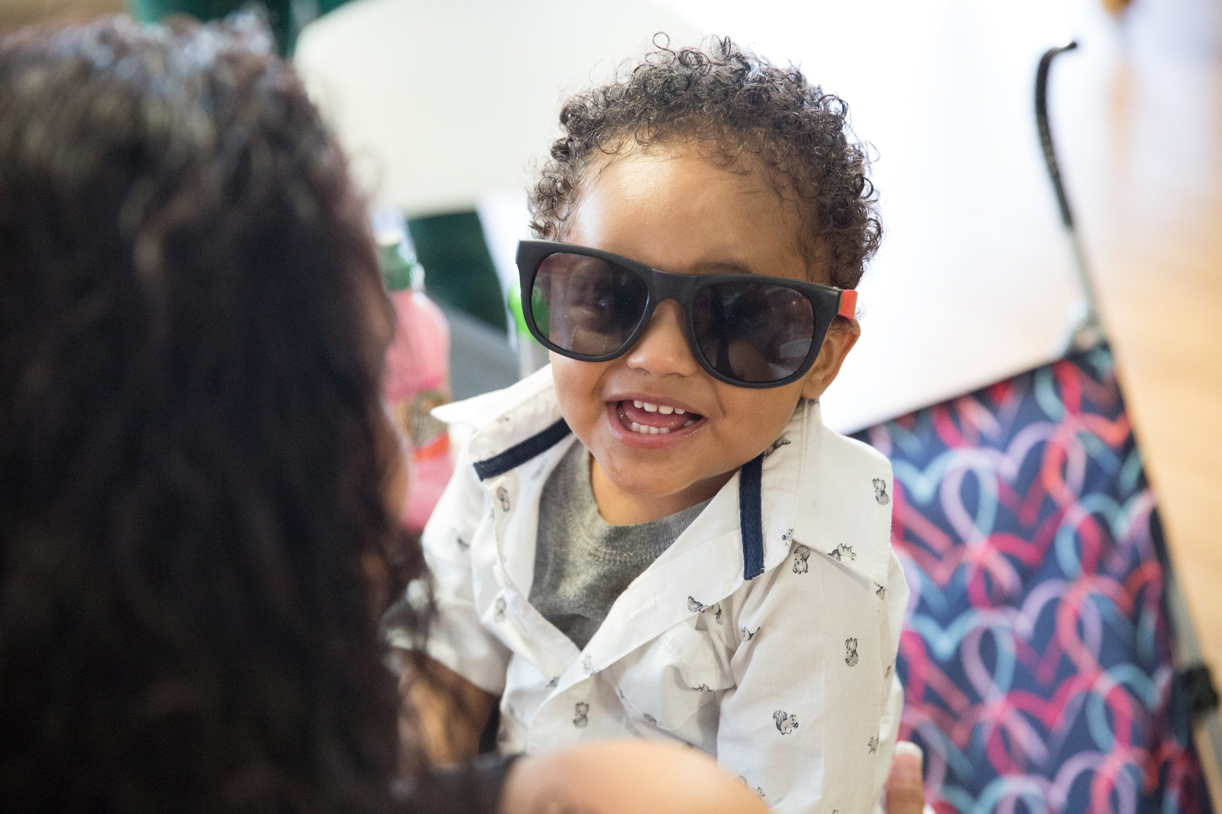 A smiling toddler wearing sunglasses looks over an adult's shoulder.