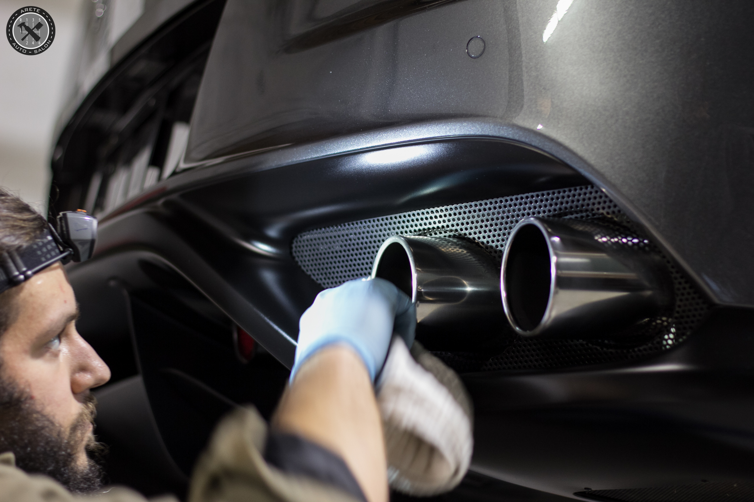 Our lead detailer polishing the exhaust tips.