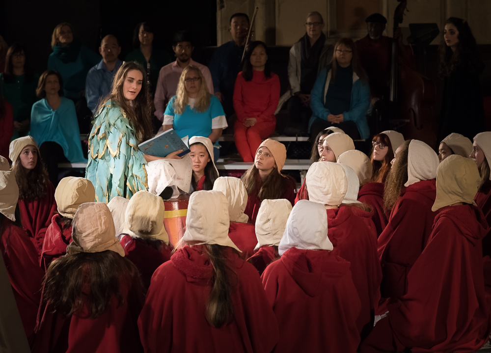 "Vireo (Rowen Sabala), awakened from her drug-induced sleep, sings the Dragon Aria to the ""afflicted girls"" (San Francisco Girls Chorus)."