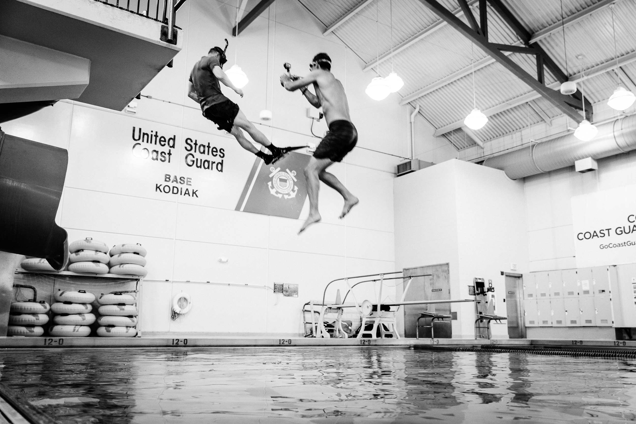 Justin Bastien diving in with a Rescue Swimmer in the USCG training facility. Kodiak Air Station, Alaska.