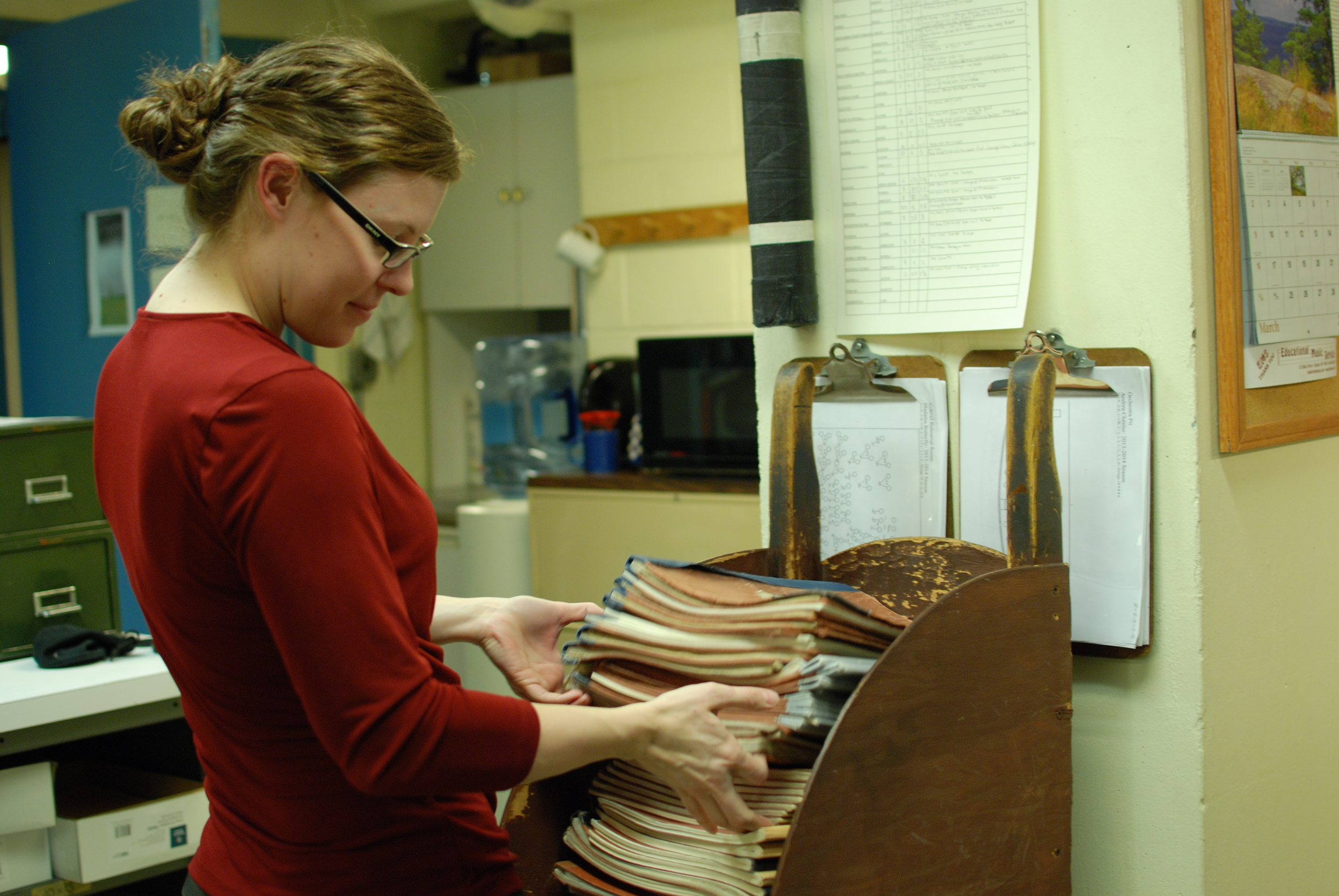 Melissa Robason counts parts collected after an orchestra rehearsal.