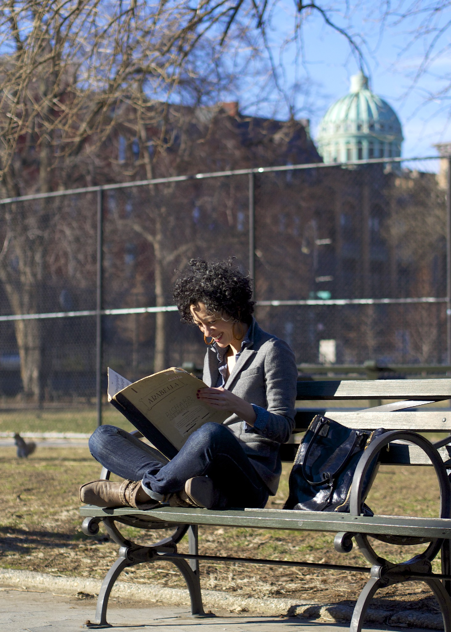 Toni peruses a part to Strauss'  Arabella  on a bench in Marcus Garvey Park, Harlem; photo credit, Bruno Eicher