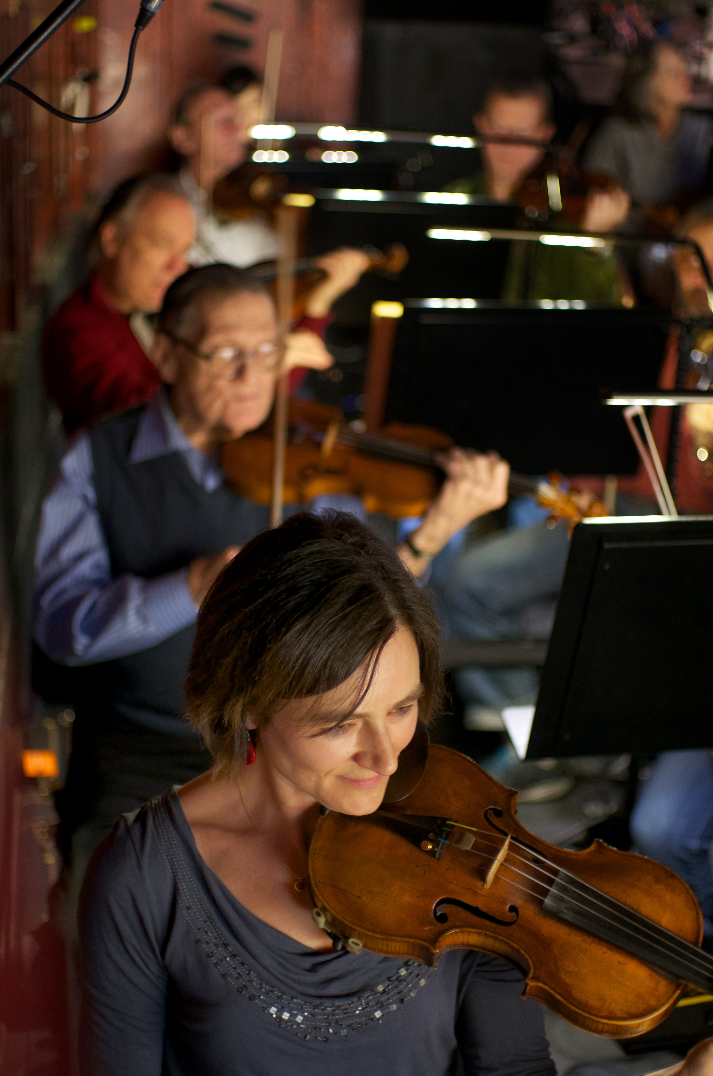 Before rehearsal: Caterina Szepes (foreground) smiles as she anticipates brain oscillation coordination with her first violin colleagues.
