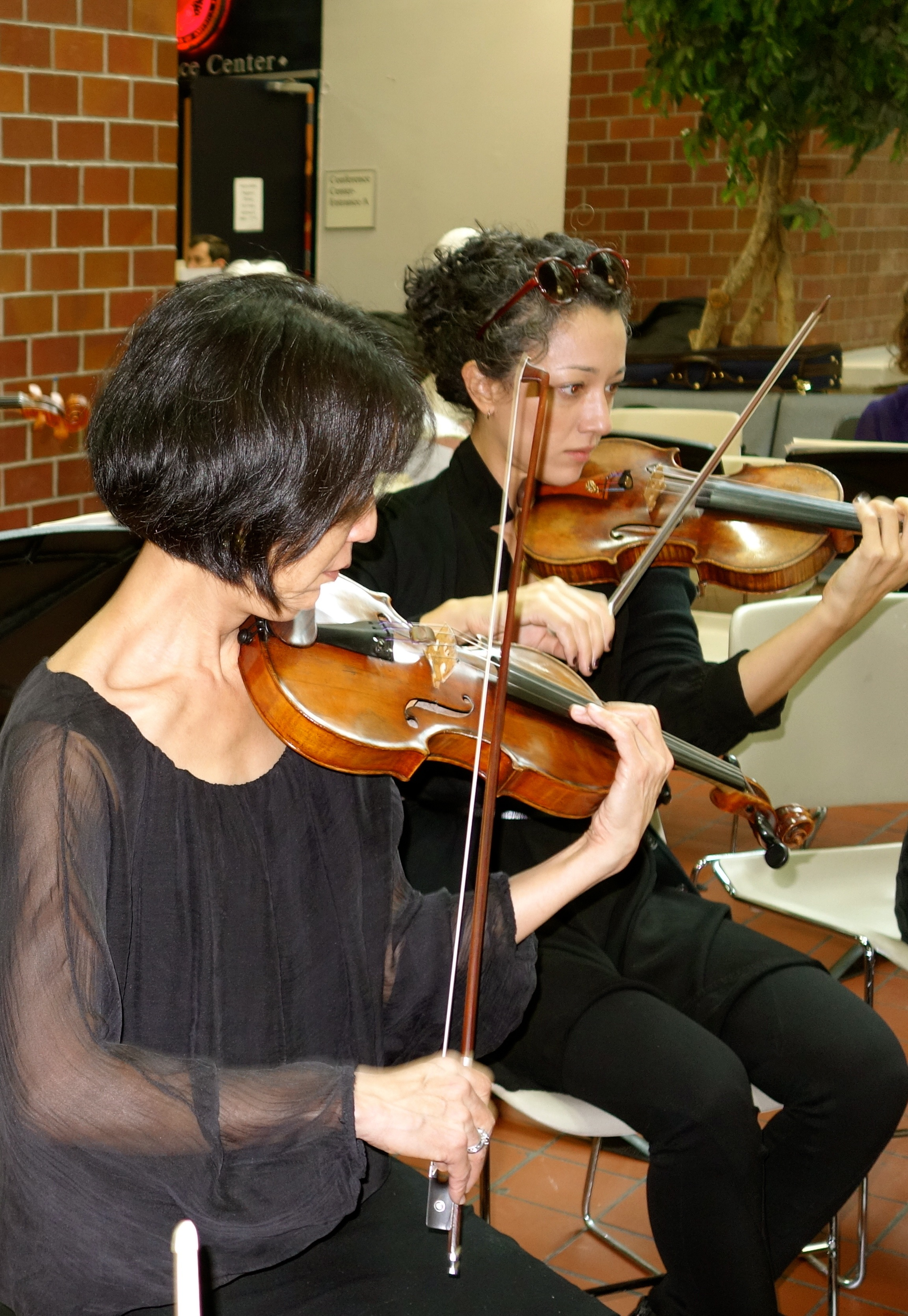 Concertmistress Nancy Wu and stand partner Toni Glickman warm up before the concert.