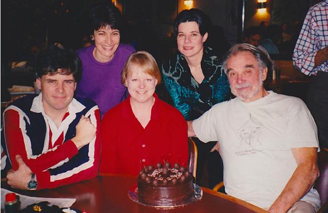 The Met Opera oboe section celebrates Richard Nass' 76th birthday in 1995. Front row: John Ferrillo, Susan Spector, and Richard Nass. Back row: Elaine Douvas, Sharon Meekins (chocolate-covered cherry cake by Elaine Douvas)