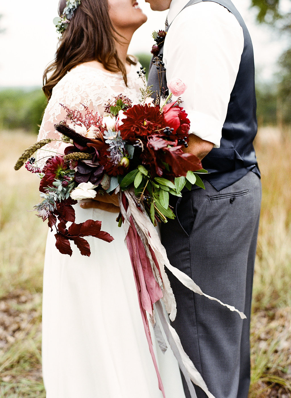 Bohemian style, red and Burgundy bridal bouquet with silk ribbon at Vista West Ranch. Petal Pushers floral event design studio located in Dripping Springs, Texas.