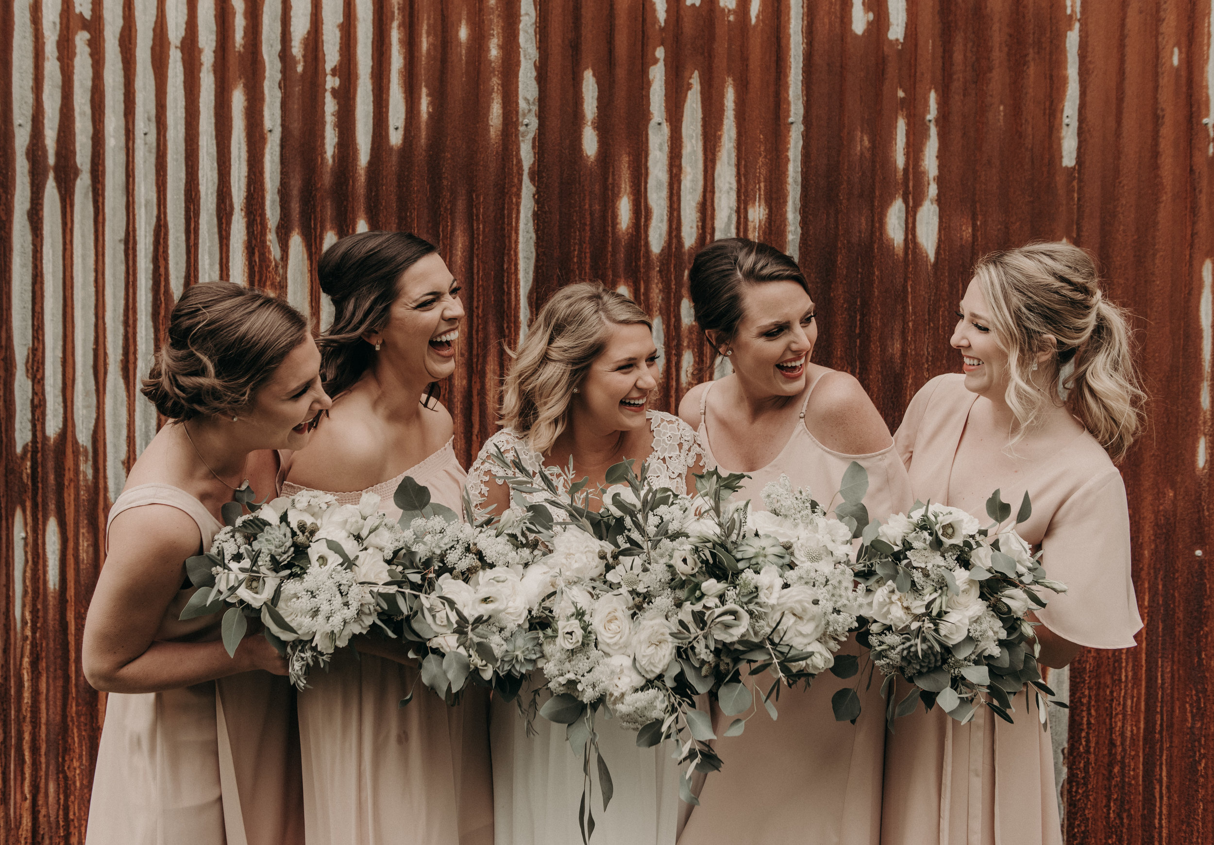 Bohemian style, wildflower inspired bridal and bridesmaid bouquets with white garden roses, eucalyptus, anemone, ranunculus at The Creek Haus. Petal Pushers floral event design studio located in Dripping Springs, Texas.