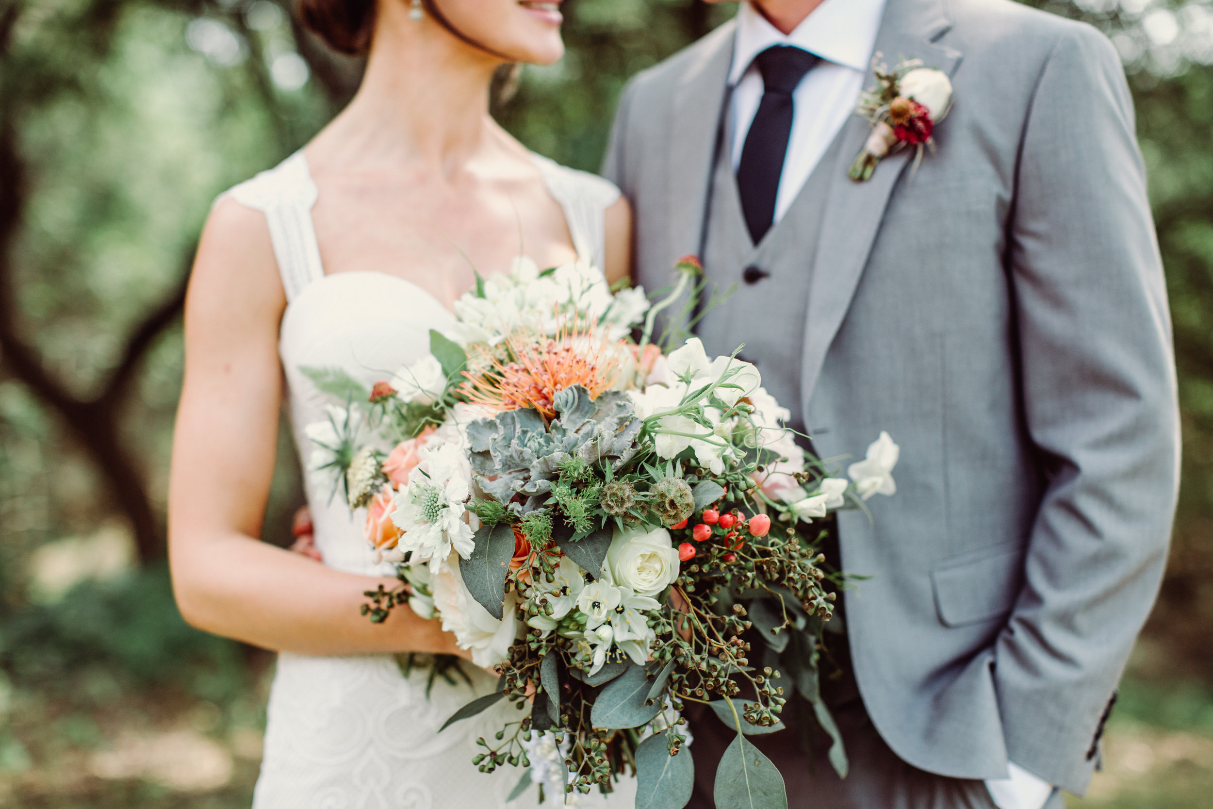 Bohemian style white with pops of orange and succulent bridal bouquet at The Creek Haus. Petal Pushers floral event design studio located in Dripping Springs, Texas.
