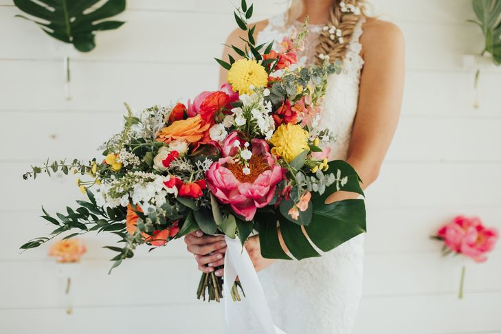 Bohemian style, tropical inspired bridal bouquet with pink, yellow, and coral charm peonies. Petal Pushers floral event design studio located in Dripping Springs, Texas.