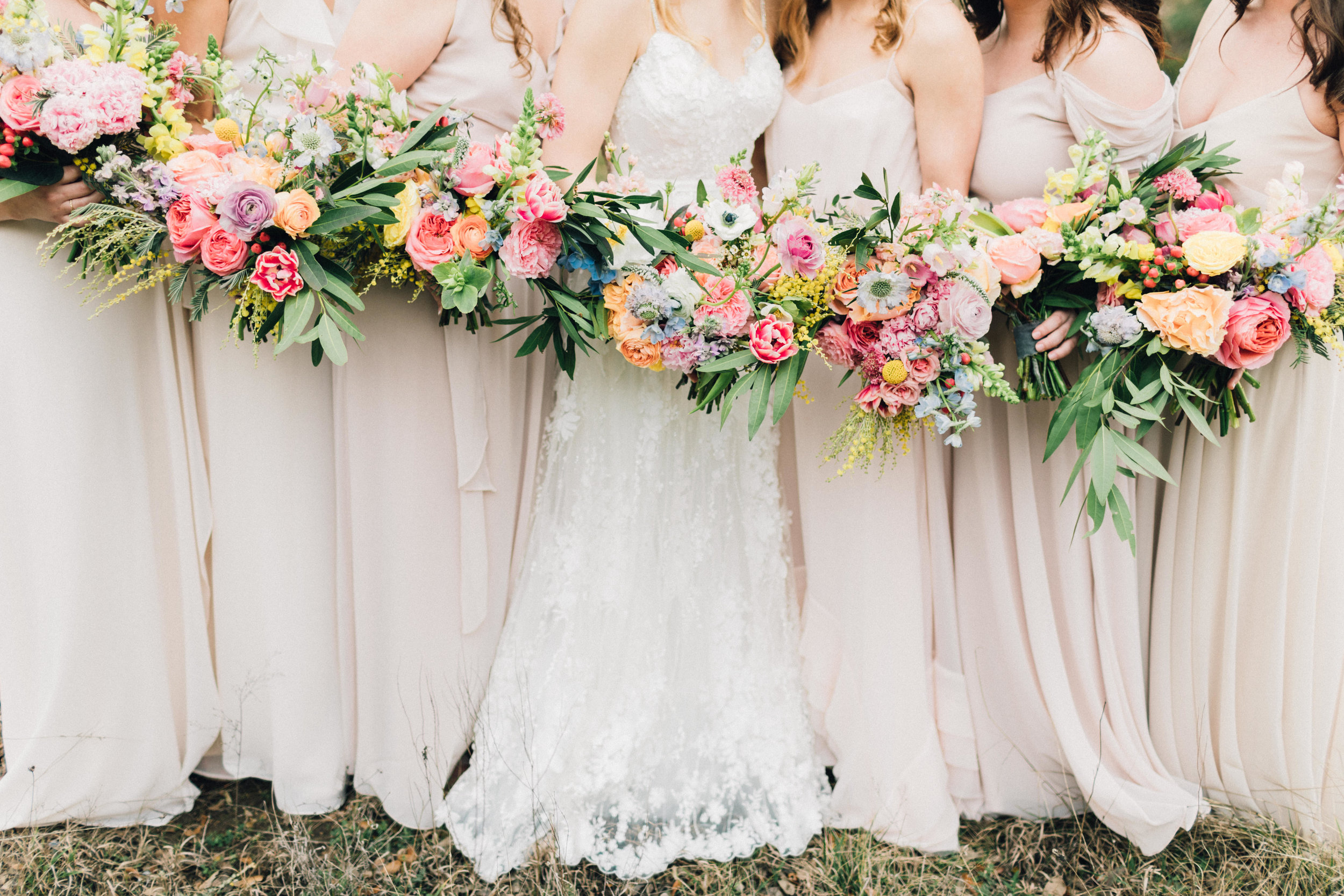 Bohemian style, colorful bridal and bridesmaid bouquets with pink, yellow, coral peonies, poppies, anemone, spray roses, ranunculus at Addison Grove. Petal Pushers floral event design studio located in Dripping Springs, Texas.