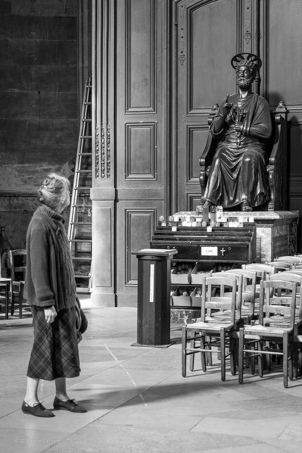 A woman gazing at Saint Peter at Église Saint-Sulpice in Paris.