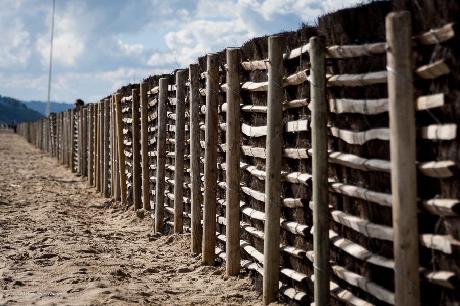 The fence along the beach in Deauville, France has many intriguing details that conjure up my memories of the day. I wish I had changed my angle so the pole wasn't visible, and to have waited until the woman wasn't peeking over the fence! My learning continues...