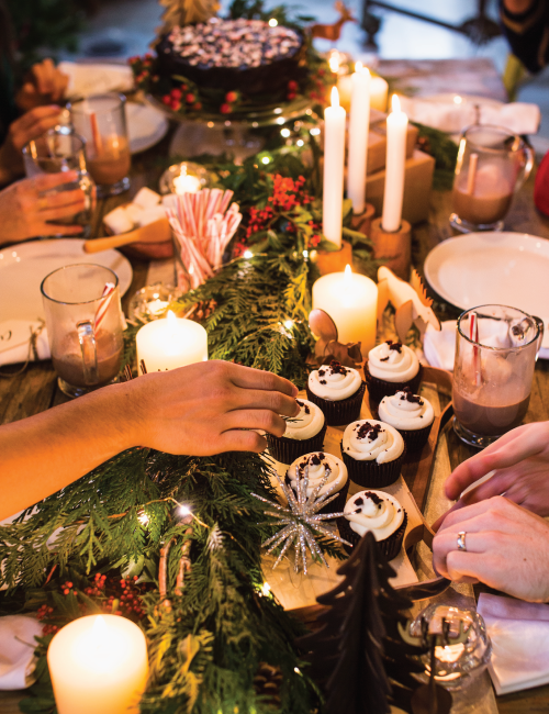 The fresh cedar garland wrapped in twinkle lights workedwell as anatural table runner.