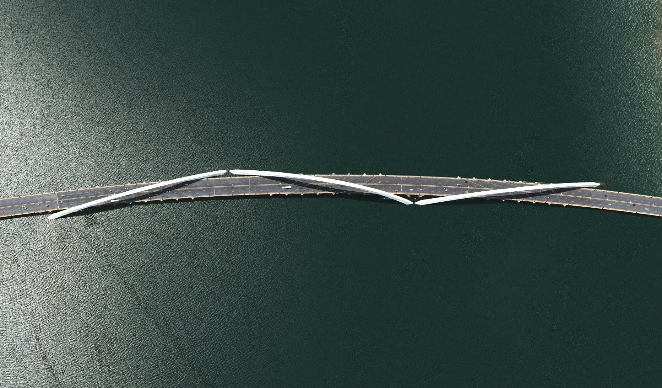 5/15/2015   Juscelino Kubitschek Bridge   Brasilia, Brazil  15°49′25″S 47°49′46″W     The Juscelino Kubitschek Bridge is a steel and concrete structure that crosses Lake Paranoá in Brasília, Brazil. The main span has four supporting pillars submerged underwater, while the deck weight is supported by three 200-foot-tall (61 m) asymmetrical steel arches that crisscross diagonally over the bridge.