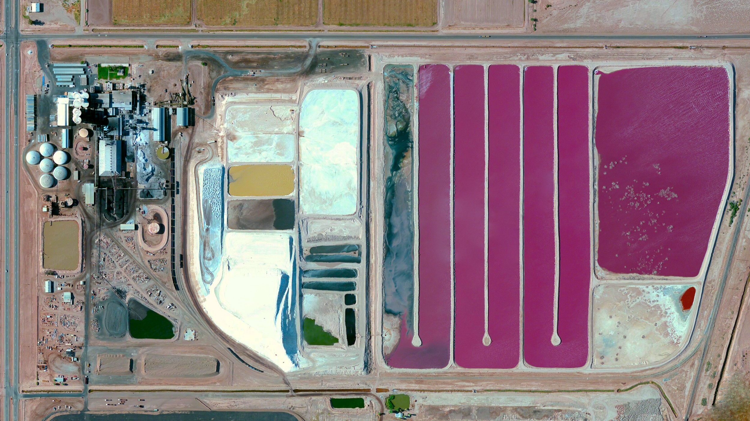 5/24/2015  Spreckles Beet Sugar Factory  Brawley, California, USA  32.905407, -115.565693      Another shot from the archive: The Spreckles Beet Sugar Factory is located in Brawley, California, USA. After machines extract sugar from sugarbeet roots, the leftover (and colorful) beet pulp is dried on a massive paved area next to the factory. The pulp is then used a major ingredient in dairy feed.