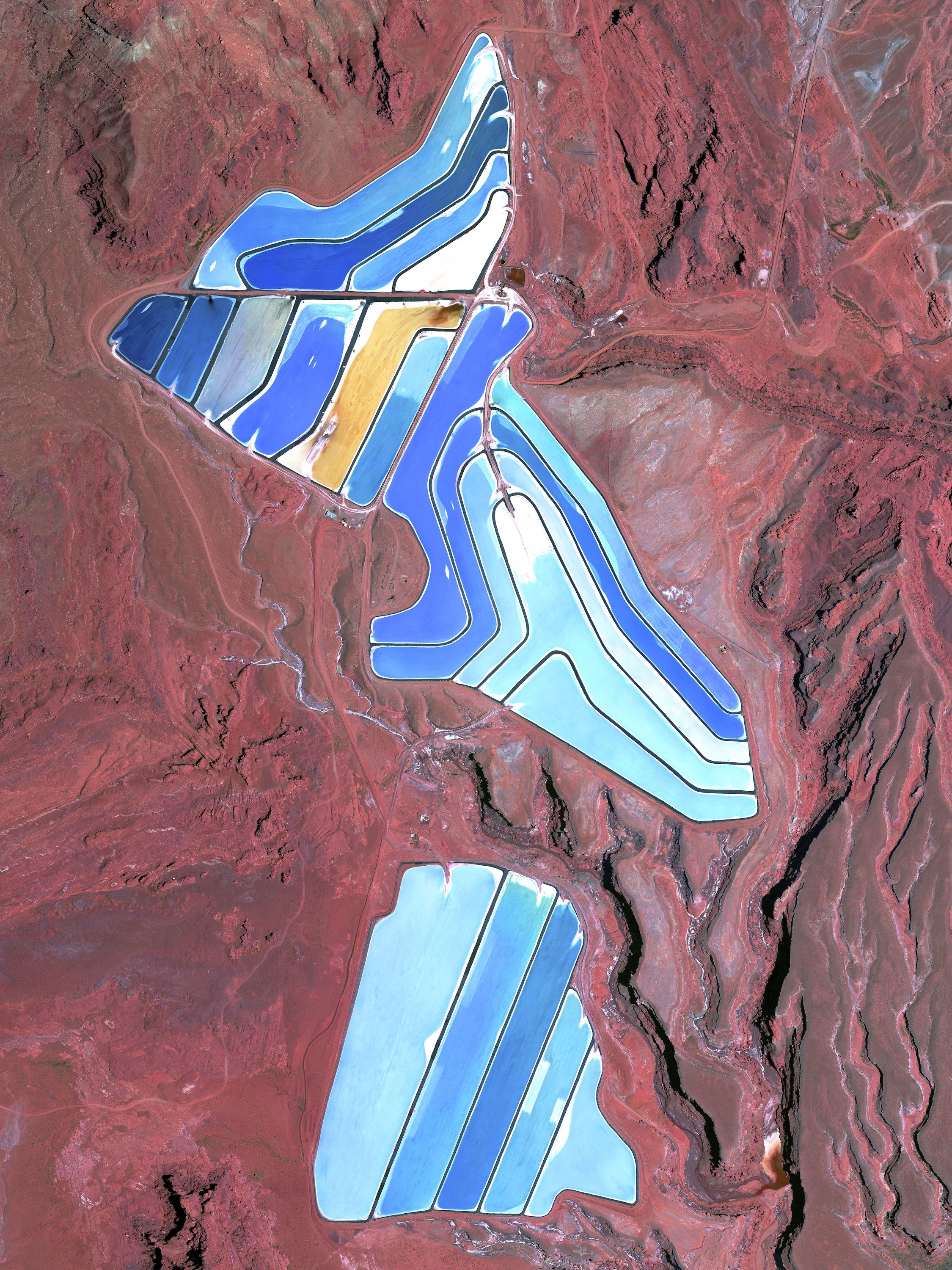 5/30/2015   Evaporation ponds of Intrepid Potash mine    Moab, Utah, USA    38°29'0.16″N 109°40'52.80″W      The Intrepid Potash Mine in Moab, Utah, USAproduces muriate of potash, a potassium-containing salt used widely by farmers in fertilizer.  The salt is pumped to the surface from underground deposits and driedin massive solar ponds that vibrantly extend across the landscape.  As the water evaporates over the course of 300 days, the salts crystallize out. So why are you seeing such vibrant colors?The water is dyed bright blue to reduce the amount of time it takes for the potash to crystallize; darker water absorbs more sunlight and heat.
