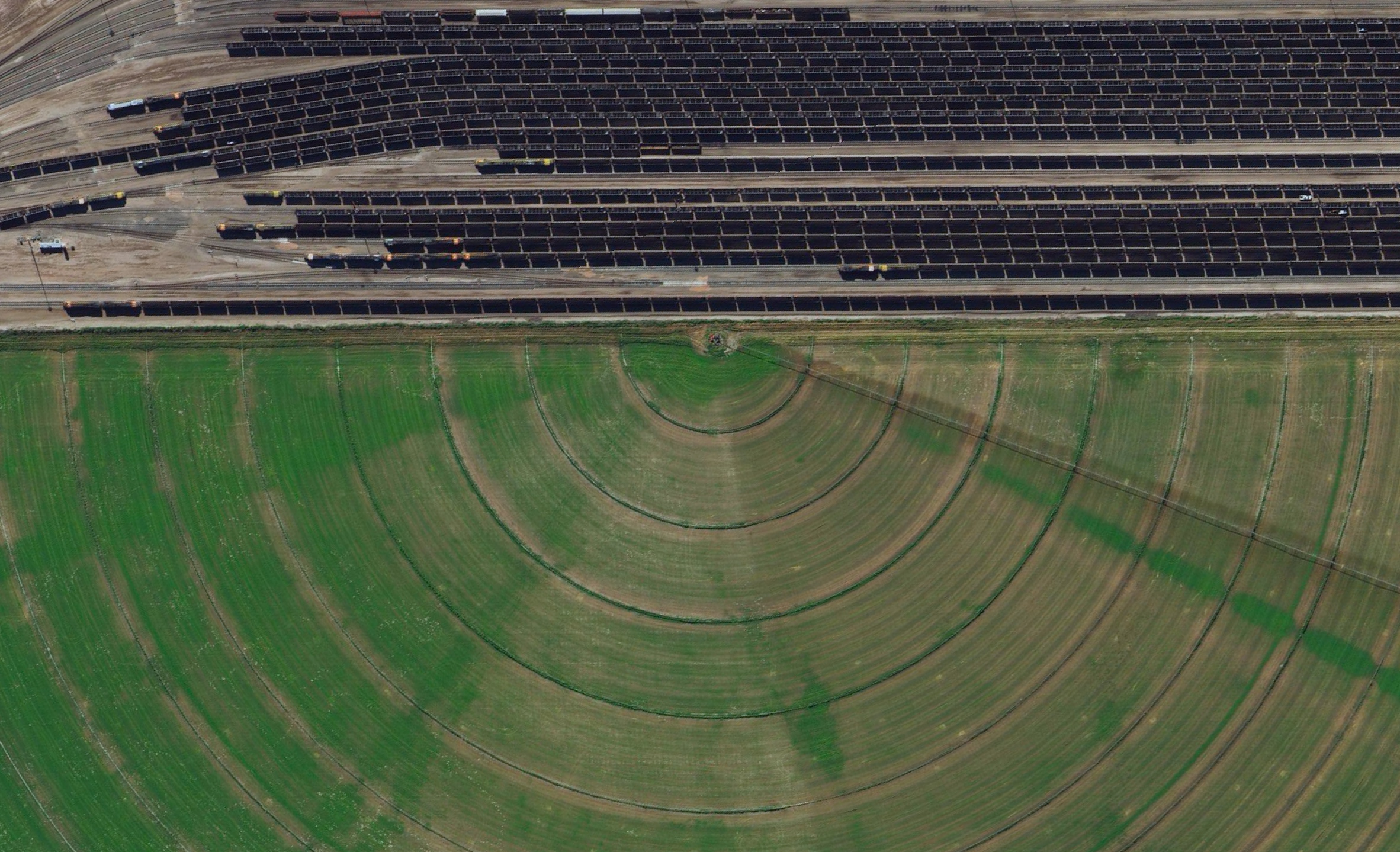 7/15/2015   Coal trains   Alliance, Nebraska, USA  42.082523321°, -102.890045721°    Coal trains - some full, others empty - idle in a railyard next to a pivot irrigation circle in Alliance, Nebraska, USA. The city is located in the Powder River Basin - one of the world's largest coal-mining areas - and serves as a stopping point for trains en route to power plants in the Midwest and Southern parts of the country.