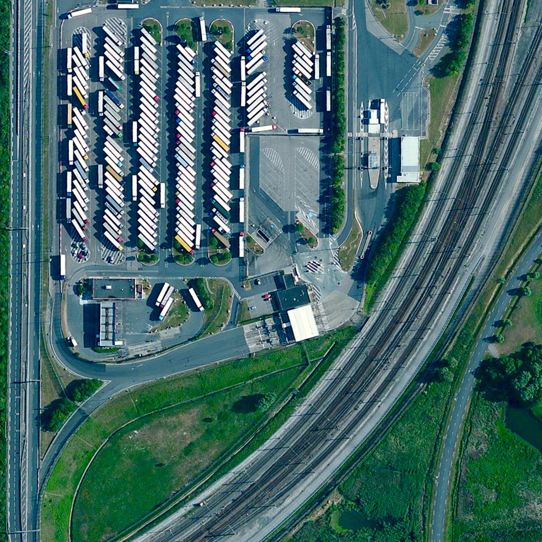 7/29/2015  Trucks at  Channel Tunnel   Calais, France  50.931745288°, 1.824167808°    Trucks sit by the entrance of the Channel Tunnel in Calais, France.  Last night more than 2,200 migrants attempted to break into the tunnel entrance  in an effort to get to Britain - 31.4 miles away via the underwater passage. This is the latest incident in an ongoing crisis in Europe where an estimated 100,000 migrants have entered the continent to flee violence and poverty in neighboring regions.