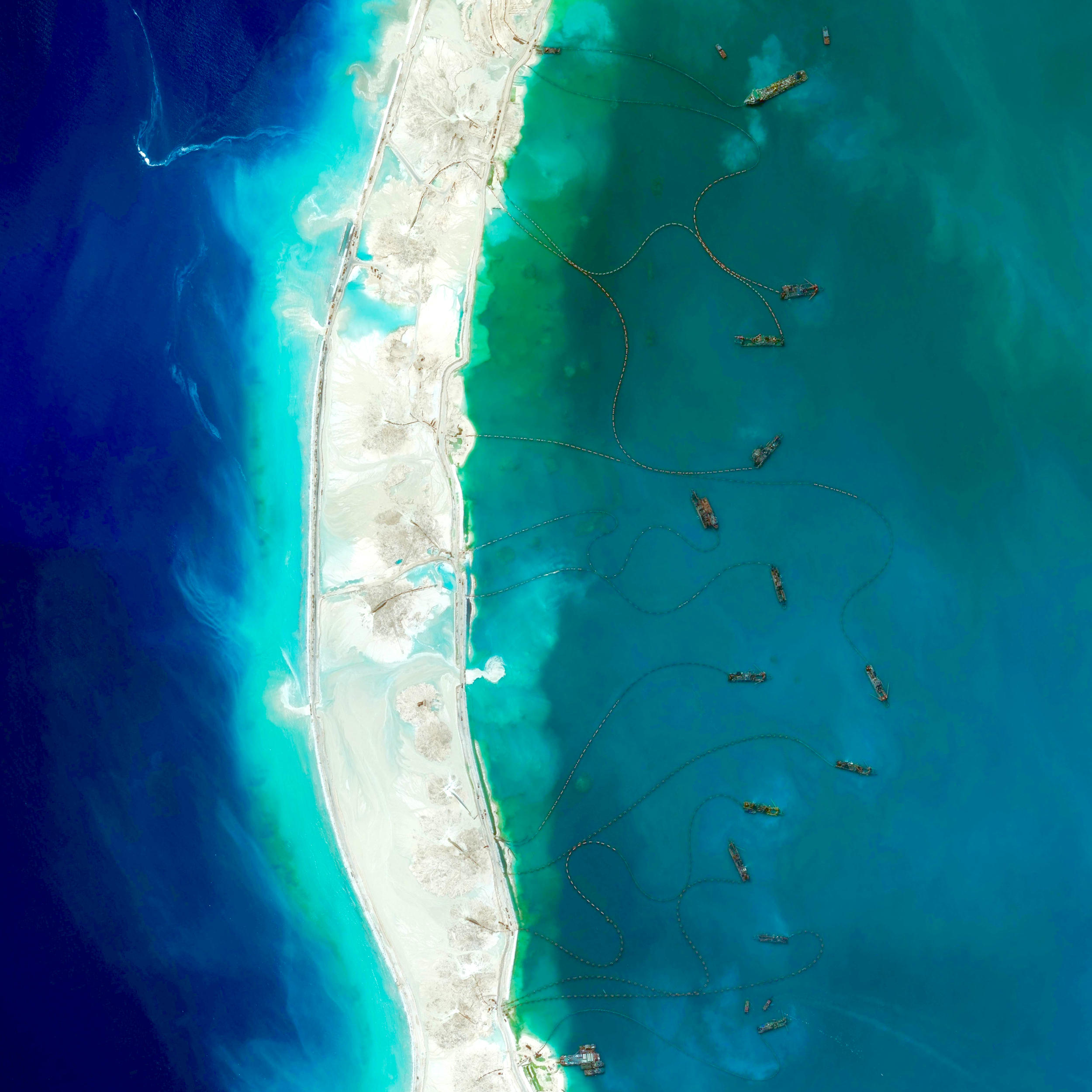 """7/31/2015   Mischief Reef   Spratly Islands, South China Sea  9°55′N 115°32′E    The New York Times published a fascinating piece this morning on Chinese island building in the South China Sea. Dredgers - the boats you see here around """"Mischief Reef"""" - pump sediment from the ocean up into floating pipes, and deposit the material onto the reef to increase land area. This enables the large-scale construction projects currently underway on the newly formed islands. See the full story  here ."""