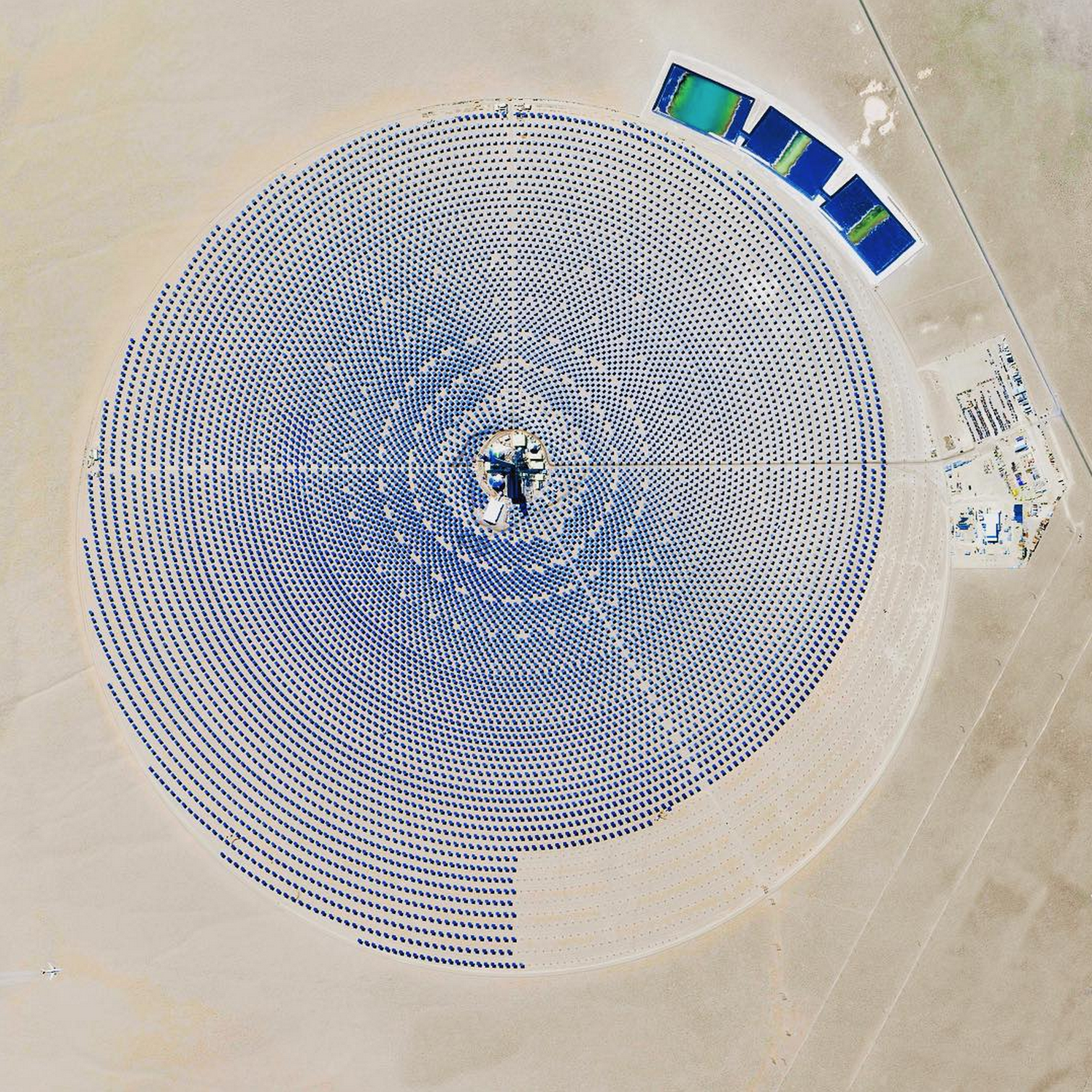 10/4/2015   Crescent Dunes Solar Energy Project   Tonopah, Nevada, USA   38°14′N 117°22′W   The Crescent Dunes Solar Energy Project near Tonopah, Nevada powers up to 75,000 homes during peak electricity periods. So how does it work? The project uses 17,500 heliostat mirrors to collect and focus the sun's thermal energy to heat molten salt flowing through a 540-foot (160 m) tall solar power tower. The molten salt then circulates from the tower to a storage tank where it is used to produce steam and generate electricity. One last thing - look closely at the lower left corner of this Overview and you'll see an airplane flying over the complex!