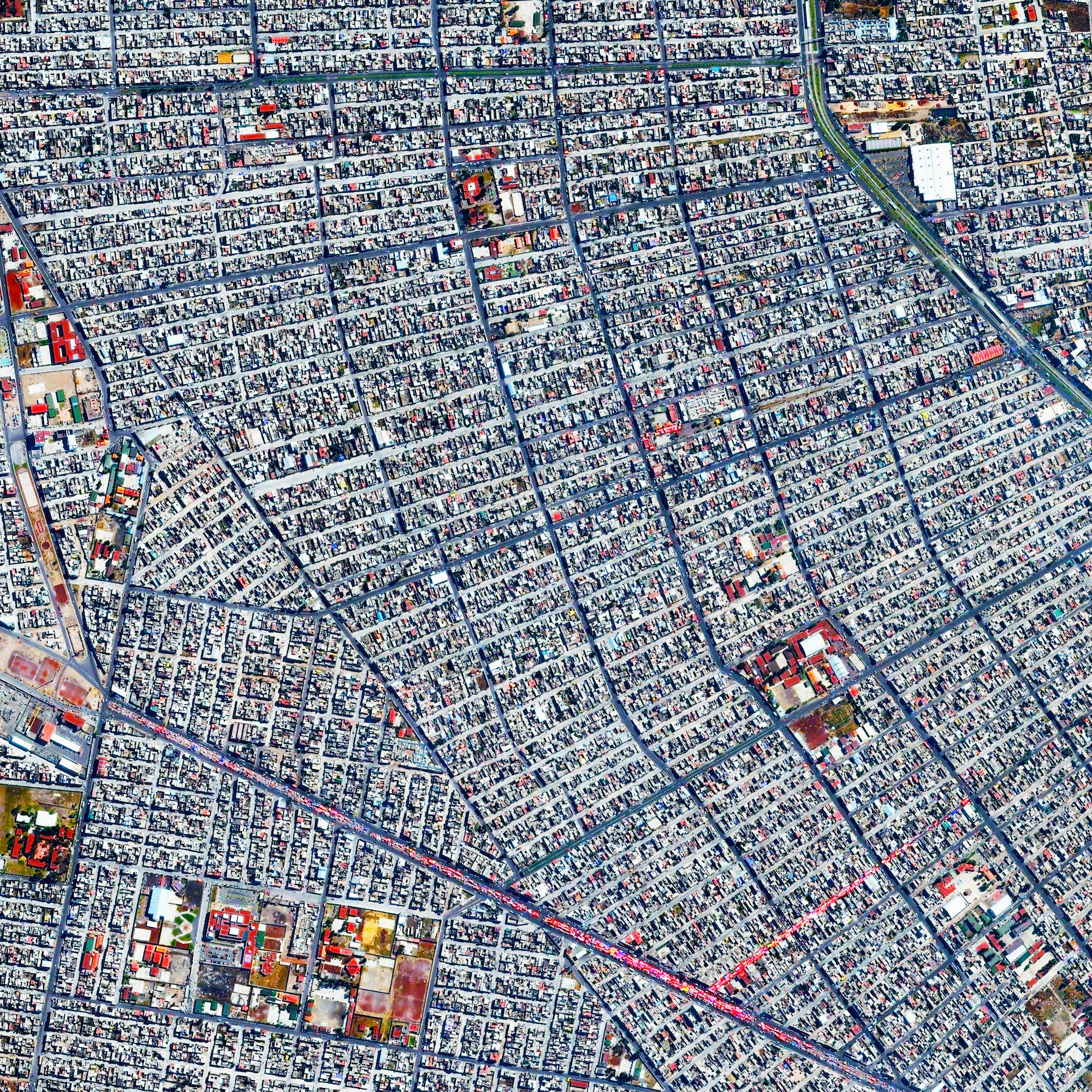 11/4/2015   Chimalhuacán   Chimalhuacán, Mexico  19.435062776°, -98.968516816°    Chimalhuacán is a city with more than 600,000 residents in the eastern part of the State of Mexico, Mexico. The colorful strip seen across the bottom of this Overview is a open-air market known as a tianguis. Here, merchants cover their stalls with vibrant canopies to protect themselves from harsh sun and inclement weather.