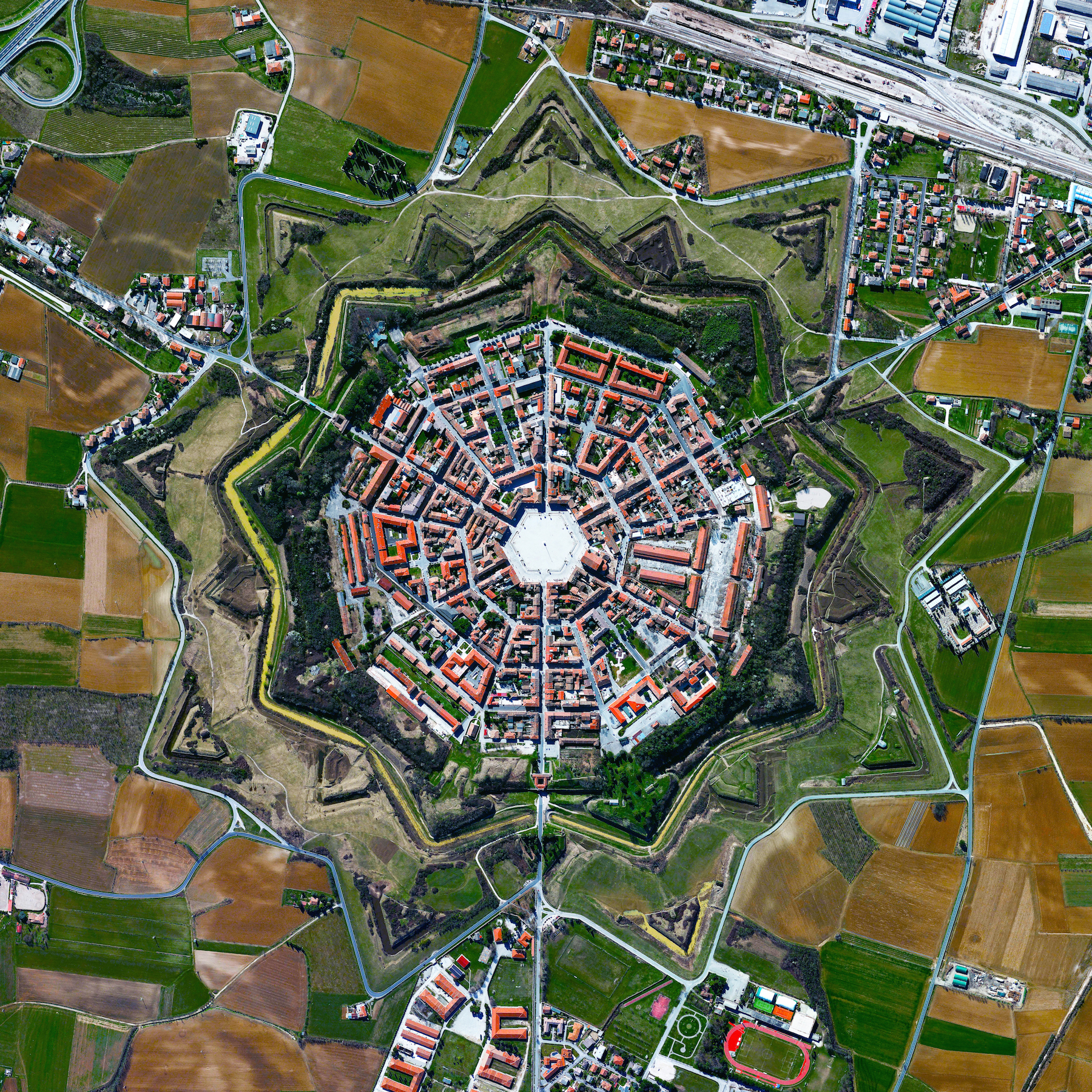 11/9/2015   Palmanova   Palamova, Italy  45.904892400°, 13.317671100°    The town of Palmanova, Italy is recognized by its concentric layout known as a star fort. The rationale for this construction was that an attack on any individual wall could be defended from the two adjacent star points by shooting the enemy from behind. The three rings that surround Palmanova were completed in 1593, 1690, and 1813.