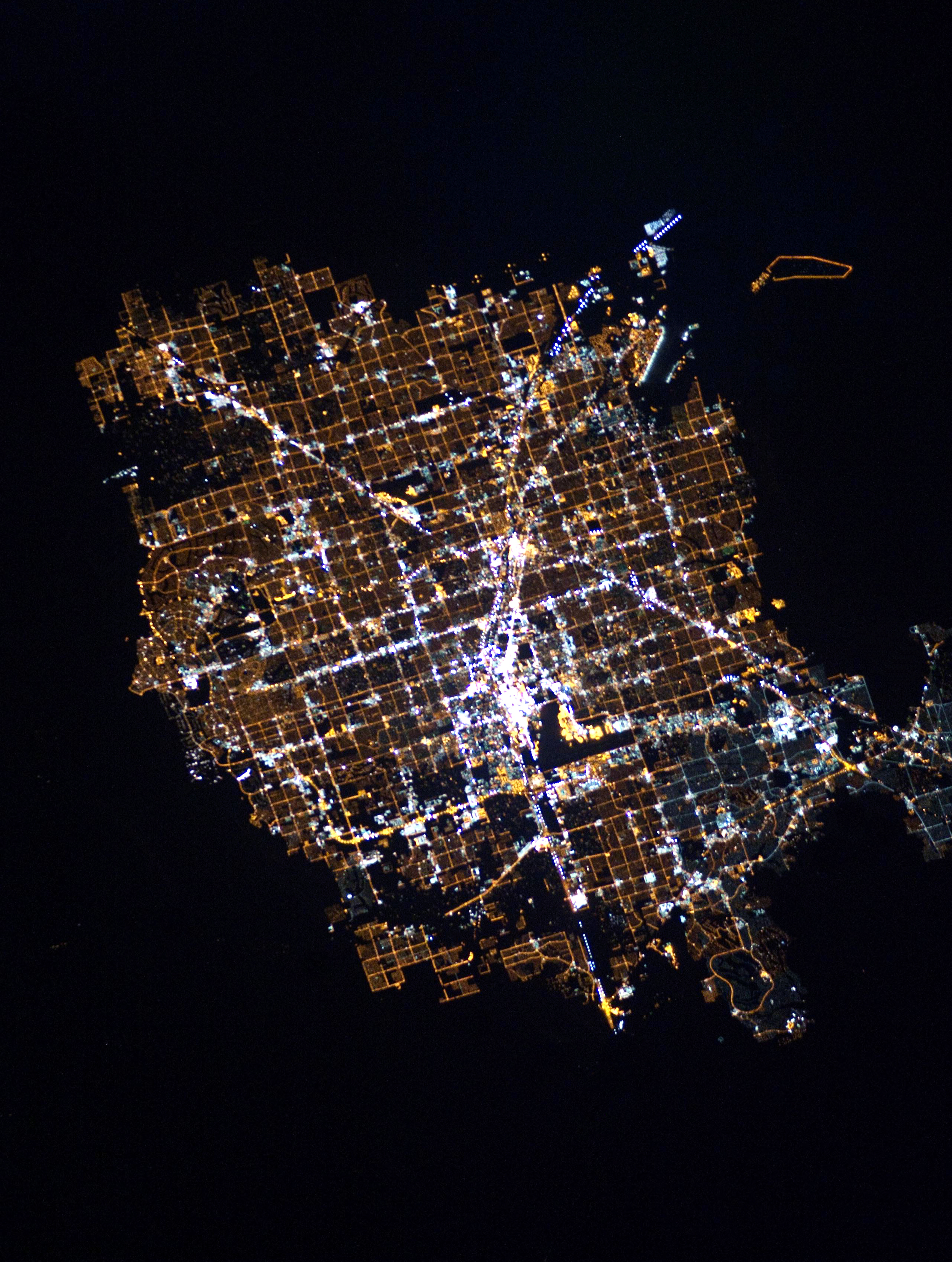 2/3/2016   Las Vegas at night   Las Vegas, Nevada, USA  36°10′30″N 115°08′11″W    The glowing lights of Las Vegas, Nevada are captured here from the International Space Station. Since the city is entirely surrounded by desert, its brightly lit grid of streets starkly contrasts the dark, undeveloped area on its outskirts. You'll also notice the Las Vegas Strip - the city's central avenue that is seen at the middle of this Overview. This particular area is one of the brightest spots on Earth due to the concentration of lights emanating from the hotels and casinos along the road.  Source imagery courtesy of NASA